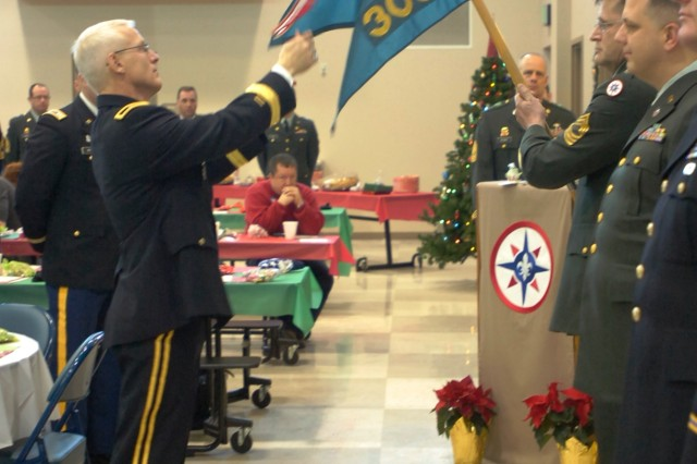 CORAOPOLIS, Pa. -- Brig. Gen. Peter S. Lennon, Commander, 316th Expeditionary Sustainment Command, attaches a streamer to the unit flag of the 305th Military History Detachment in recog-nition of the Meritorious Unit Citation during Family Day here Dec. 18. Family Day was a combination holiday celebration and awards presentation for Soldiers of the 316th ESC. The 305th MHD is a subordinate unit of the 316th ESC which has deployed to multiple combat zones. The 305th MHD also received the Re-serve Officer Association Outstanding U.S. Army Reserve Small Unit Award to recognize for their outstanding service throughout the years. The unit is also recognized for their deployment to Af-ghanistan in 2006-2008 for producing the first historical docu-mentation of Operation Enduring Freedom. In 2009 and 2010 the 305th MHD was asked by the White House Historical Association to produce historical documents about the White House Trans-portation Agency.