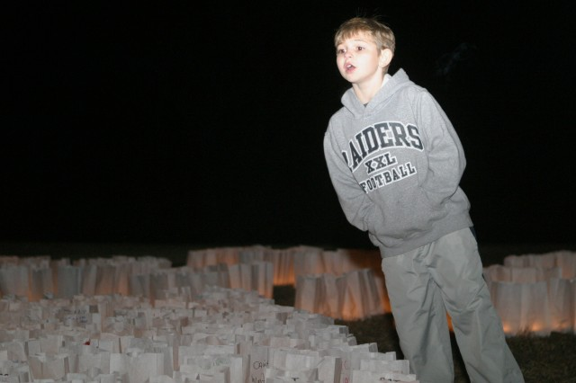 Joseph Kildow, Bluemont Elementary school second-grader, Fort Riley, Kan., looks for the luminary bag bearing his father's name at the BOSS Candle Lighting Ceremony Dec. 17 at Riley's Conference Center.