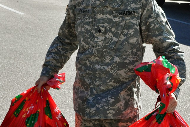 FORT HOOD, Texas-Spc. Jamie Fifield, an early warning systems operator for the Headquarters and Headquarters Battery, 41st Fires Brigade, carries bags of toys into the Charles B. Allen Hall where Leon County residents delivered more than 500 toys to the children and families members of the Rail Gunners, Dec. 20.