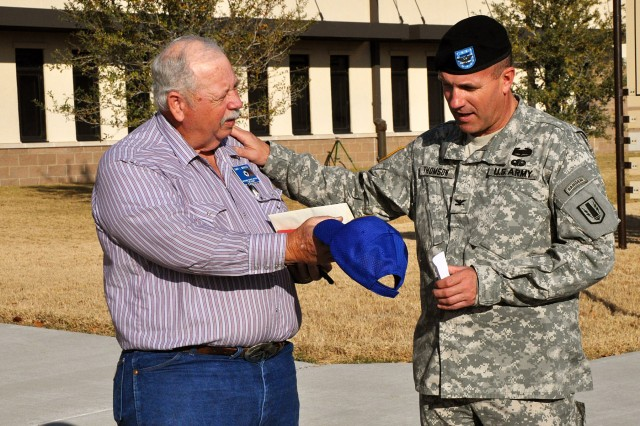 FORT HOOD, Texas-Gary Maples (left), a veterans service officer for Leon County, gives Col. John Thomson, brigade commander for the 41st Fires Brigade, his favorite cap after he delivered toys to the brigade, Dec. 20.