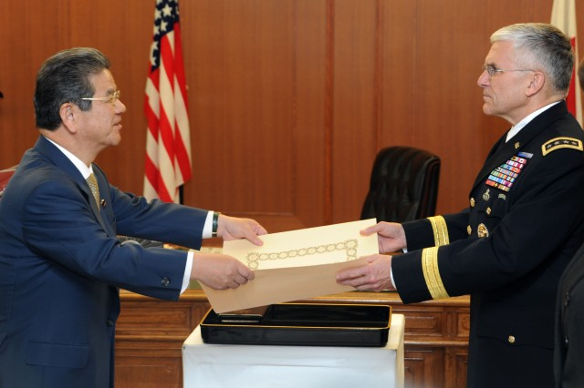 Japanese Defense Minister Toshimi Kitazawa, left, presents the proclamation he read to Gen. George W. Casey Jr., right, chief of staff of the U.S. Army, prior to awarding him the Order of the Rising Sun during a Dec. 21, ceremony held at the Japanese Ground Self-Defense Forces headquarters at Camp Ichigaya. The Order of the Rising Sun is Japan's second most prestigious decoration.