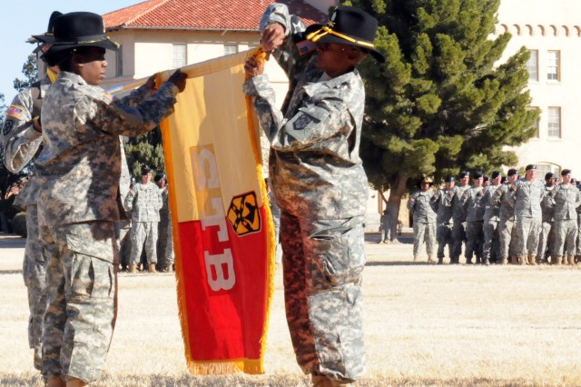 """Lt. Col. Litonya Wilson, commander, 15th Special Troops Battalion, 15th Sustainment Brigade and Command Sgt. Maj. Dolishia King, the battalion's sergeant major, uncases the battalion's colors during an Uncasing Ceremony on Noel Field here Dec 8 which officially established the """"Wranglers"""" as members of Team Bliss. (U.S. Army Photo by Spc. Valerie Lopez, Headquarters, Fort Bliss)"""