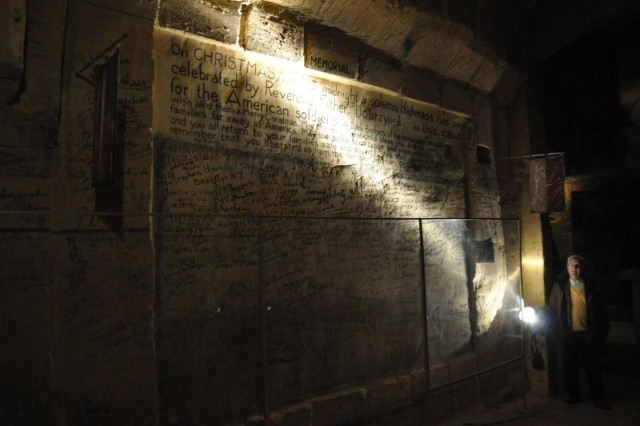 Behind the glass is a tribute to the 300 U.S. Service Memebers who celebrated Christmas Eve in 1944 is on a wall in the De Schark Caves where U.S. Soldiers etched their names in charcoal before departing the next day to face the Battle ofthe Bulge. The original 48-star U.S. flag and the local Maastricht flag still hangs there.