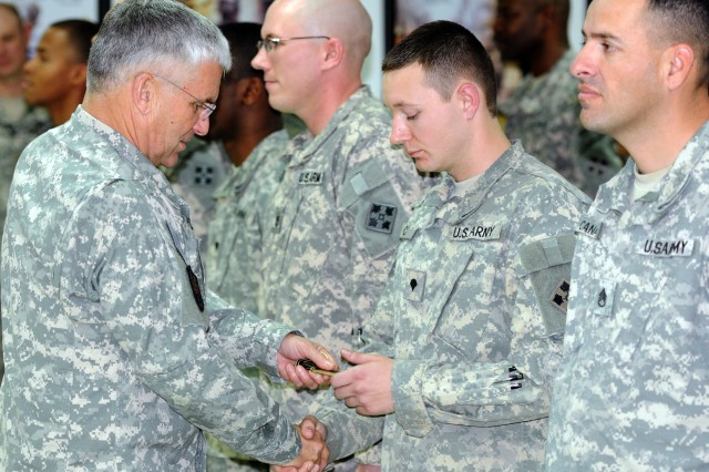 "CONTINGENCY OPERATING BASE SPEICHER, Iraq - U.S. Army Chief of Staff Gen. George W. Casey, Jr., presents a coin to Spc. James Curtis, information technology specialist assigned to Company C, Division Special Troops Battalion, 4th Infantry Division, during a special coining ceremony for Soldiers serving with U.S. Division-North, deployed in support of Operation New Dawn, Dec. 24, 2010. The Army's top ranking officer visited with Soldiers of Task Force Ironhorse, serving at COB Speicher, Christmas Eve, to thank the men and women in uniform for their service to the nation, especially during the Holiday Season. Curtis, who hails from Pasadena, Md., said it feels good to be individually recognized amongst the hardworking Soldiers of the U.S. Division-North Communications Section, who are responsible for keeping the ""Ironhorse"" Division Headquarters computers mission capable."