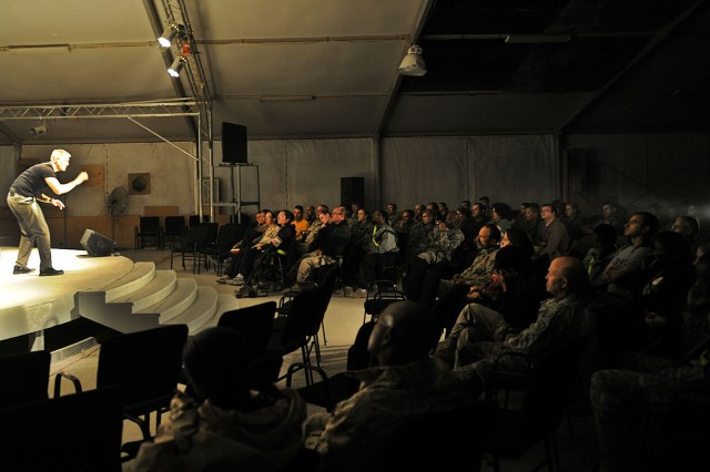 """A crowd of nearly 100 people watch as U.S. Air Force Maj. Kevin Whaley, an intelligence, surveillance and reconnaissance collection manager for Regional Command-South, performs Charles Dickens' """"A Christmas Carol"""" at Kandahar Airfield, Afghanistan, Dec. 19. Whaley adapted the play to include references understood by deployed members, e.g., replacing the monetary denotations such as farthing and pence with Eagle Cash Card."""