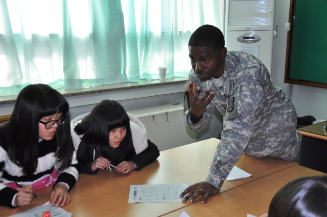 A U.S. Army Soldier assigned to the 501st Special Troops Battalion, 501st Sustainment Brigade, helps students understand the meaning of a word during English lessons at the Seokjeon Junior High School during a visit Dec. 16, 2010.  The visit was arranged as part of the unit's Good Neighbor Program, a program which emphasizes the long-standing Korean-American relationship on the Korean peninsula. U.S. Army photo by Pvt. Sung Kwang Jae