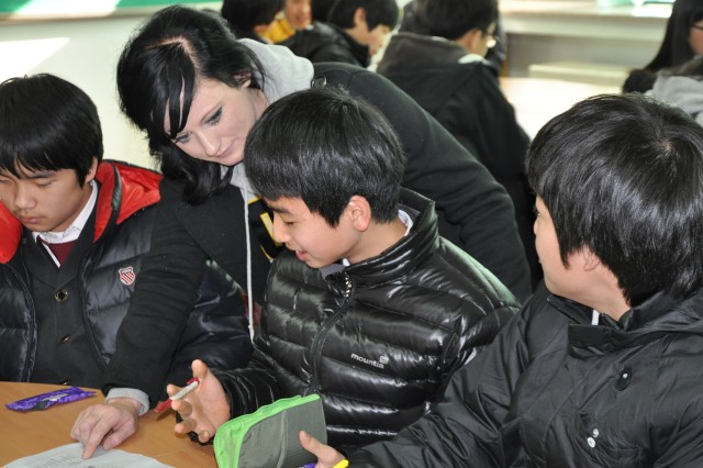 A U.S. Army Soldier assigned to the 501st Special Troops Battalion, 501st Sustainment Brigade, assists a student with his pronunciation during English lessons at the Seokjeon Junior High School during a visit Dec. 16, 2010.  The visit was arranged as part of the unit's Good Neighbor Program, a program which emphasizes the long-standing Korean-American relationship on the Korean peninsula. U.S. Army photo by Pvt. Sung Kwang Jae/501st Sustainment Brigade