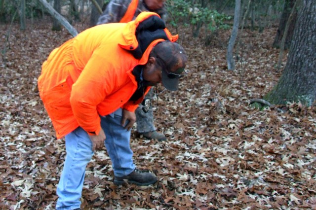 Charlie Downs (front), a Blossom Point Research Facility maintenance mechanic, assists hunter Alan Ranoull in tracking a possible wounded deer during one of the regular hunts at the Army facility in southern Maryland Dec. 4.""