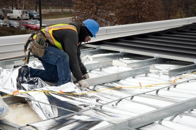 Emanuel Burgess, of Pioneer Roofing Systems, is part of the team constructing a solar thermal roof on Building 601 at the Army's Adelphi Laboratory Center, in Adelphi, Md.