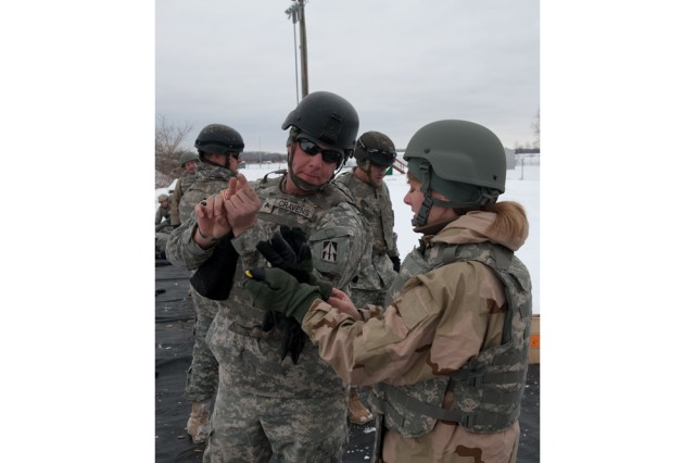 Cpl. Kevin Cravens, with the Range Training Team at Camp Atterbury Joint Maneuver Training Center, Ind., explains how to aim an M4 carbine to Anne Williams of the Civilian Expeditionary Workforce, Dec. 16. Part of the CEW's training included weapons familiarization with the M4 carbine and M9 9mm pistol.