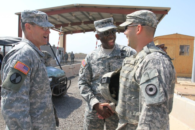 """U.S. Army Command Sgt. Maj. Mark Ripka, U.S. Africa Command (AFRICOM) senior enlisted leader (left to right), and Gen. William """"Kip"""" Ward, U.S. AFRICOM commander, greet Staff Sgt. Joshua Moore, 2nd Combined Arms Battalion, 137th Infantry Regiment, Kansas Army National Guard, during a holiday visit Dec. 25 to Camp Lemonnier, Djibouti.   Ward and Ripka met with troops, participated in a promotion ceremony and served dinner to soldiers, sailors and airmen serving in the Horn of Africa."""