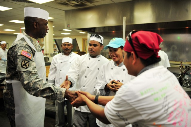 """U.S. Army Gen. William """"Kip"""" Ward,  U.S. Africa Command (AFRICOM) commander, greets Pacific Architects and Engineers (PAE) employees before serving Christmas dinner Dec. 25 at Camp Lemonnier, Djibouti.  Ward and Sgt. Maj. Mark Ripka, AFRICOM senior enlisted leader, brought holiday greetings to troops, participated in a promotion ceremony and served dinner to soldiers, sailors and airmen serving in the Horn of Africa."""