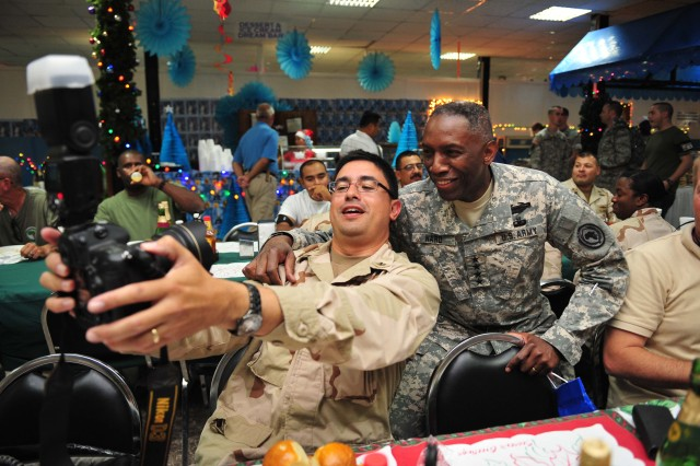 """U.S. Army Gen. William """"Kip"""" Ward,  U.S. Africa Command (AFRICOM) commander, poses for a photo with U.S. Navy Mass Communication Specialist 1st Class Joseph Garza, Camp Lemonnier Public Affairs Office, during Christmas dinner Dec. 25.   Ward and Sgt. Maj. Mark Ripka, AFRICOM senior enlisted leader, visit troops stationed at Camp Lemonnier, Djibouti, for the holidays.    Ward and Ripka met with troops, participated in a promotion ceremony and served dinner to soldiers, sailors and airmen serving in the Horn of Africa."""