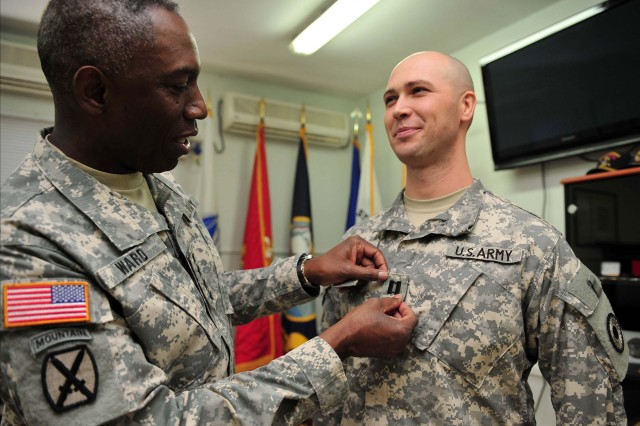 "U.S. Army Gen. William ""Kip"" Ward, U.S. Africa Command (AFRICOM) commander (left), promotes 1st Lt. Jason Dickey, 2nd Combined Arms Battalion, 137th Infantry Regiment, Kansas Army National Guard, to the rank of captain Dec. 25.   Ward and Sgt. Maj. Mark Ripka, AFRICOM senior enlisted leader, visit troops stationed at Camp Lemonnier, Djibouti, for the holidays.    Ward and Ripka met with troops, participated in a promotion ceremony and served dinner to soldiers, sailors and airmen serving in the Horn of Africa."