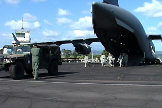 A C-17 crewmember from the 535th Airlift Squadron ground-guides a Humvee belonging to the U.S. Army Pacific Contingency Command Post Deployable Assessment Team B off of a C-17 Dec. 7, at Hilo International Airport, Hawaii.