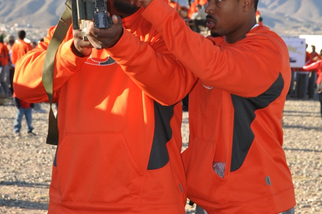 FORT BLISS, Texas (December 28, 2010) Micanor Regis (left) and Cory Nelms, both defensive tackles with the University of Miami Hurricanes, examine some military hardware at Abernethy Obstacle Course during their visit to Fort Bliss, Dec. 28.