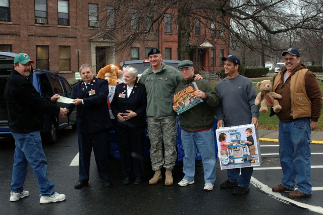 Arsenal Commander Col. Mark F. Migaleddi takes a moment in December to pose with representatives from the National Federation of Federal Employees Local #2109 and the Troy Salvation Army during the handing over of more than 600 toys to the Salvation Army.