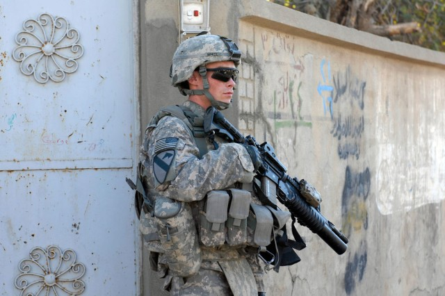 Sgt. Justin White, an infantryman with Company B, 2nd Battalion, 7th Cavalry Regiment, 4th Advise and Assist Brigade, 1st Cavalry Division, provides security during a partnered patrol in Qara Qosh, Iraq, with Iraqi Security Forces, Dec. 20.