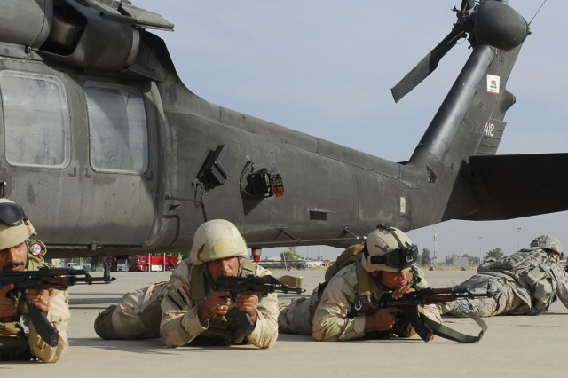 "Soldiers from the 12th Iraqi Army Division practice firing from the prone position after exiting a UH-60 Blackhawk during ""Devil's Eve"" air assault."