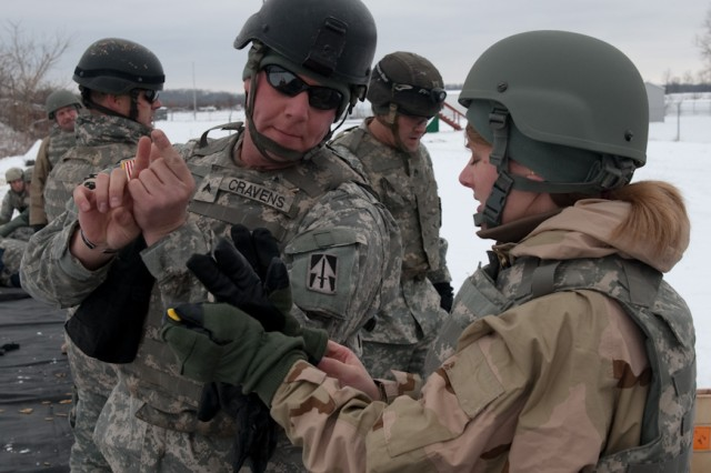 Cpl. Kevin Cravens, with the Range Training Team at Camp Atterbury Joint Maneuver Training Center, Ind., explains how to aim an M4 carbine to Anne Williams of the Civilian Expeditionary Workforce at Camp Atterbury Dec. 16; part of the CEW's training included weapons familiarization with the M4 carbine and M9 9mm pistol.