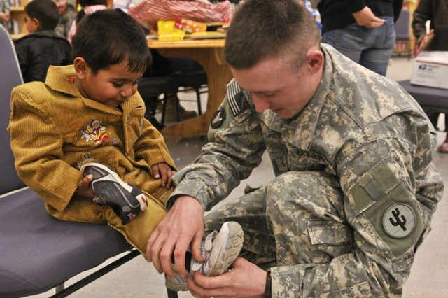 Staff Sgt. Travis Hill helps an Iraqi youngster try on a new pair of shoes during a Children's Day for orphans held at the MWR Center-North, Contingency Operating Base Speicher, Dec. 17.