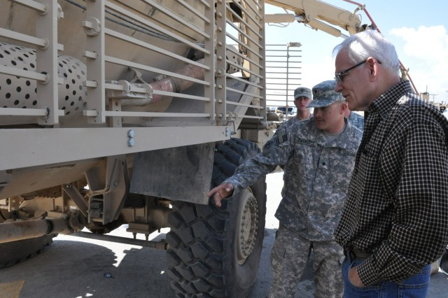 Spc. Jose Zamora, a member of Route Clearance Package 38 at Forward Operating Base Shank in eastern Afghanistan, shows Malcolm O'Neill, assistant secretary of the Army for Acquisition, Logistics and Technology, damage to his Buffalo vehicle caused by an improvised explosive device blast. Product Manager-Assured Mobility Systems, supported by the 3rd Battalion, 401st Army Field Support Brigade, maintains and repairs specialized route clearance vehicles.