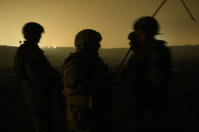 """CONTINGENCY OPERATING SITE MAREZ, Iraq - Soldiers assigned to 5th Battalion, 82nd Field Artillery, 4th Advise and Assist Brigade, 1st Cavalry Division, observe illumination rounds recently fired from an M109A6 Self-Propelled Howitzer as they light up the night sky over Mosul, Iraq, Dec 31. The """"Black Dragon"""" Soldiers used the opportunity to prepare for an upcoming artillery gunnery and add a unique twist to the New Year's Eve celebration. The 4th AAB, 1st Cav. Div. is currently deployed to Iraq in support of Operation New Dawn until late 2011."""