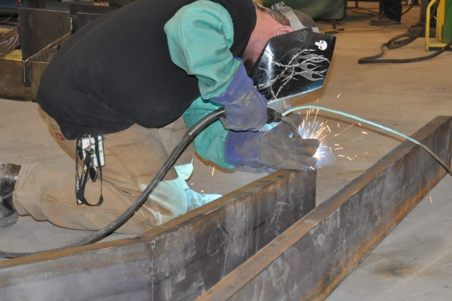 AECOM-CACI FIRST Allied Trades team member Christopher Jones uses a plasma cutter on the channel iron, the main piece of the Bastogne bumper. The bumper was developed in a joint effort between two Soldiers from the 426th Brigade Support Battalion, 1st Brigade Combat team, and members of the AECOM-CACI Allied Trades team located at the 3-401st AFSBn.