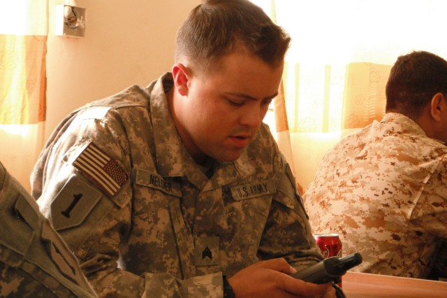 """Sgt. William Melcher, with Company B, 1st Battalion, 63rd Armor Regiment, 2nd Advise and Assist Brigade, 1st Infantry Division, United States Division Aca,!"""" Center, inspects a GPS device during land navigation training Dec. 14, in Baghdad."""