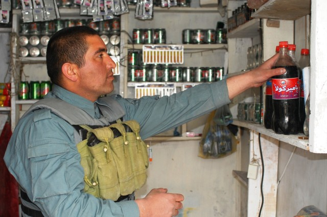 A member the Central Unit, a Quick Reactionary Force of the Afghan National Police, prepares to buy some soda at the unit store.