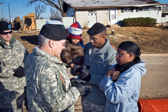 U.S. Army Chief of Staff Gen. George W. Casey Jr., front left, speaks with Capt. Lamonte Russell and his wife about being displaced from their home by a recent tornado on Fort Leonard Wood, Mo., Jan. 4, 2011. Russell is assigned to the 3rd Chemical Brigade. The New Year's Eve tornado damaged several other military houses.