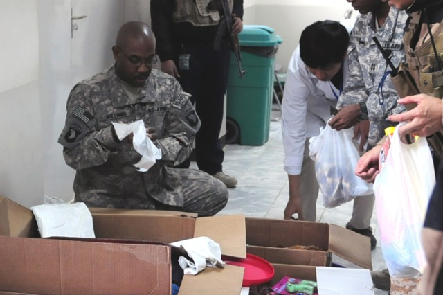 BAGRAM AIRFIELD, Afghanistan - U.S. Army Capt. Charles Choi, Task Force Med tactical operations center operations battle captain, and a native of Queens, N.Y., hands out bags of toys and clothes to Afghan children at Bagram Airfield's Korean Hospital Jan. 2. The gifts were donated by members of Company C, Headquarters and Headquarters Battalion, 101st Airborne Division. (Photo by U.S. Army Sgt. Grant Matthes, Combined Joint Task Force-101 Public Affairs)