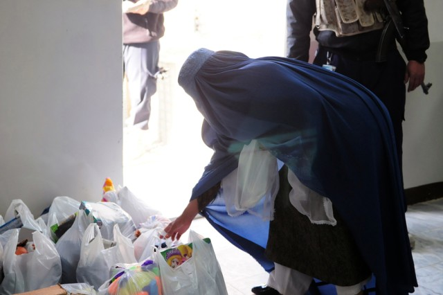BAGRAM AIRFIELD, Afghanistan - A local Afghan woman picks up bags of toys and clothes at Bagram Airfield's Korean Hospital Jan 2. The gifts were donated by members of Company C, Headquarters and Headquarters Battalion, 101st Airborne Division. (Photo by U.S. Army Sgt. Grant Matthes, Combined Joint Task Force-101 Public Affairs)