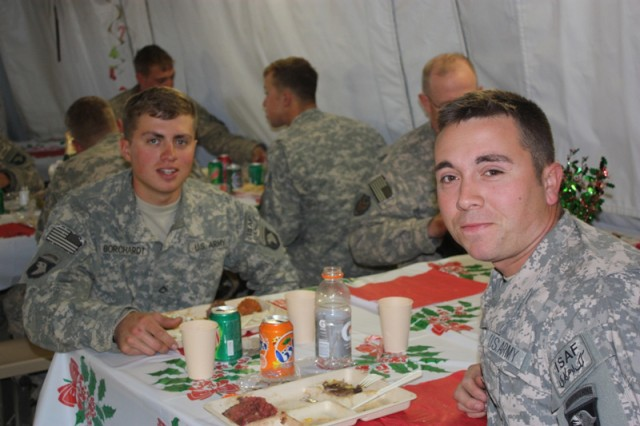 GHAZNI PROVINCE, Afghanistan - U.S. Army Sgt. Joel Borchardt (right) eats dinner with his brother, U.S. Army Pfc. James Borchardt, Dec. 24. This is the first time in 11 months the brothers have seen one another, despite both serving in Afghanistan. Joel, a liaison for Task Force Rakkasan to TF White Eagle stationed at Forward Operating Base Ghazni, visited Andar District, where James was serving. It was a complete surprise for the younger brother. Both Soldiers are from Tuscon, Ariz. (Photo by Polish Capt. Dariusz Kudlewski, Task Force White Eagle Public Affairs)