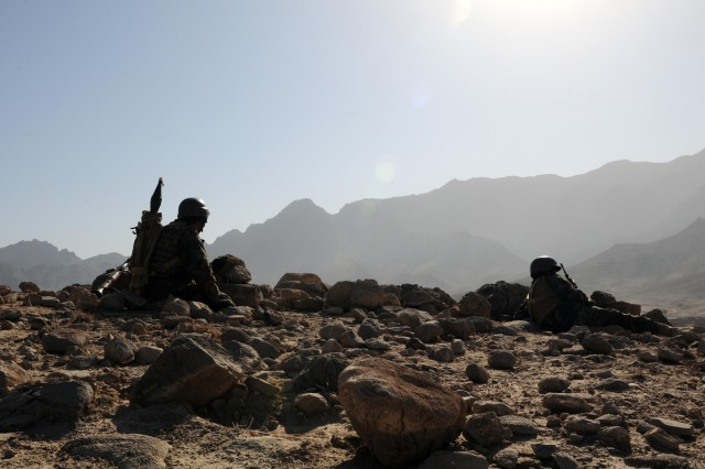 TANGI VALLEY, Afghanistan - Two Afghan National Army soldiers from the 4th Kandak, 4th Brigade, 205th Corps, rest after hiking three miles through rugged terrain. ANA and Australian forces pushed their way through the valley to set up security for the construction of a new forward operating base Dec. 28, 2010. (Photo by Spc. Jonathan Thomas, 16th Mobile Public Affairs Detachment.)