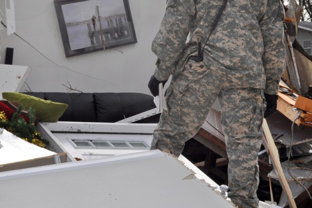 Army soldier looks at a wedding photo hanging from a wall in military housing damaged during a tornado on Fort Leonard Wood, Mo., Dec. 31, 2010.