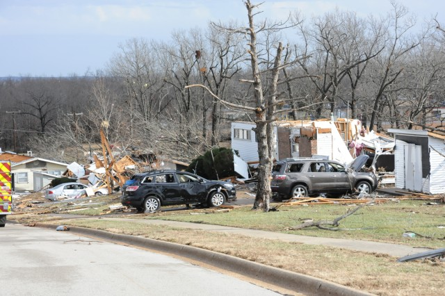 Damaged cars sit in front of destroyed homes on Fort Leonard Wood, Mo., after a tornado swept through family housing Dec. 31, 2010.