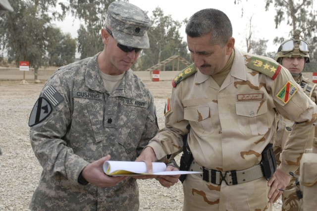 Lt. Col. John Cushing (left), commander, 1st Squadron, 9th Cavalry Regiment, 4th Advise and Assist Brigade, 1st Cavalry Division, discusses the training schedule with staff Col. Mohamed Olwan, commander of 1st Battalion, 11th Brigade, 3rd Iraqi Army Division, at al-Ghuzlani Warrior Training Center, Iraq.