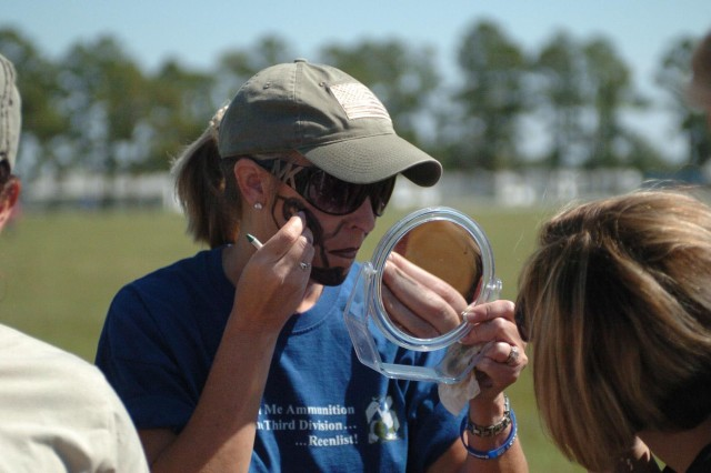 A combat wife shows motivation and Spartan sportsmanship by painting her face prior to maneuvering through her first obstacle during an event at the Combat Spouse's Badge Event held at Donovan Field, Oct. 3.