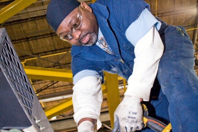 Ricko English works atop a Stryker in Anniston Army Depot's Combat Vehicle Repair Facility.