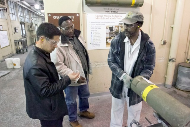 ADMC explosives operator Alfonza Curry, right, and supervisor Clyde Hill explain TOW missile recycling operations to Maj. Park San Yoon, left, of the Republic of Korea.
