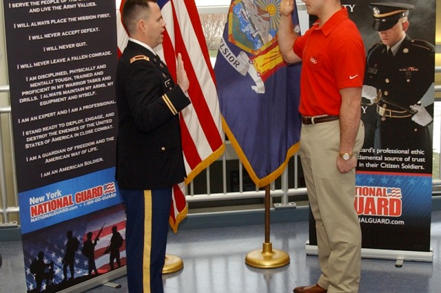 Lt. Col. Steve Rowe, commander of the New York Army National Guard's Recruiting and Retention Command, administers the oath of enlistment to bobsledder Justin Olsen, who won a Gold Medal at the 2010 Vancouver Winter Olympics as a member of a four-man bobsled team, at the Division of Military and Naval Affairs headquarters in Latham, N.Y., Jan. 6.