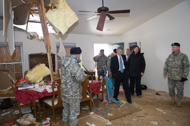 Secretary of the Army John McHugh walks through military housing damaged by a tornado that struck Fort Leonard Wood, Mo., Dec. 31.