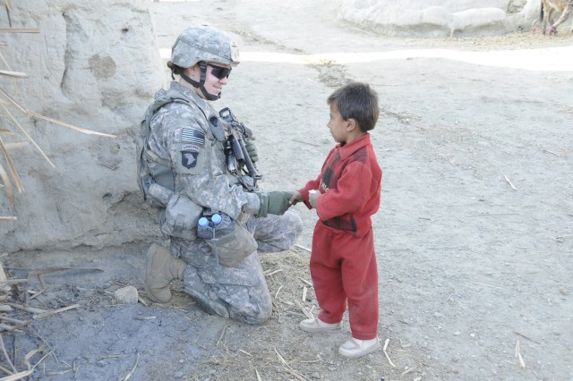 Spc. Lauren Hyman, and armored vehicle driver for the 64th Military Police Company, based at Combat Outpost Fortress, Afghanistan, greets an Afghan child during a foot patrol in Noor Gal District, Jan. 3.
