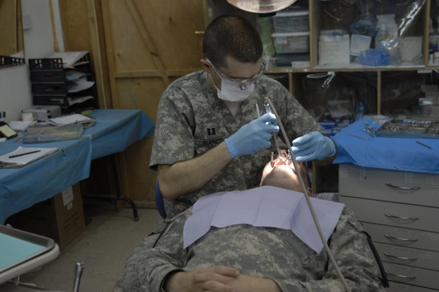 COTINGENCY OPERATING SITE MAREZ, Iraq - Capt. Bernardo Bianco, a dentist assigned to Company C, 27th Brigade Support Battalion, 4th Advise and Assist Brigade, 1st Cavalry Division, seals a filling at the troop medical clinic for 1st Lt. Frank Siler Dec. 29. Bianco, a native of Orlando, Fla., cares for all the dental needs of the brigade while deployed in support of Operation New Dawn.