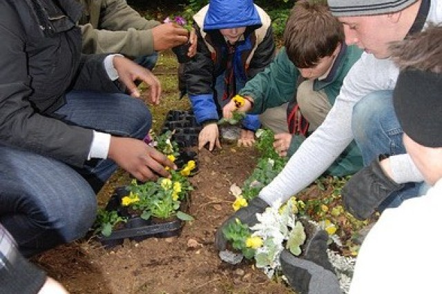 Heidelberg BOSS Soldiers and children tend graves at a children's cemetery in Frankfurt, Germany for Make a Difference Day. The event was just one of many the Soldiers participated in throughout the year.