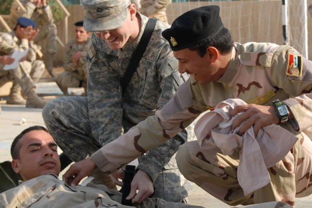 Pfc. Clinton Cochran (center), a medic with Company C, 299th Brigade Support Battalion, 2nd Advise and Assist, 1st Infantry Division, United States Division - Center, helps loosen the straps on a litter Jan. 5, after an Iraqi Army soldier demonstrated the proper techniques to secure a simulated casualty onto the litter at Forward Operating Base Constitution, Iraq. The IA went through a two-day course on combat life saving skills.