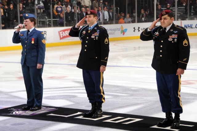 Medal of Honor recipient Staff Sgt. Salvatore Giunta (center) and Staff Sgt. Erik Gallardo salute as Sgt. Cindy Scott of the Canadian Air Command Band (left) sings during opening ceremonies at the L.A. Kings game against the Toronto Maple Leafs at the Staples Center in Los Angeles on Monday, Jan. 10, 2011. (C) NHL