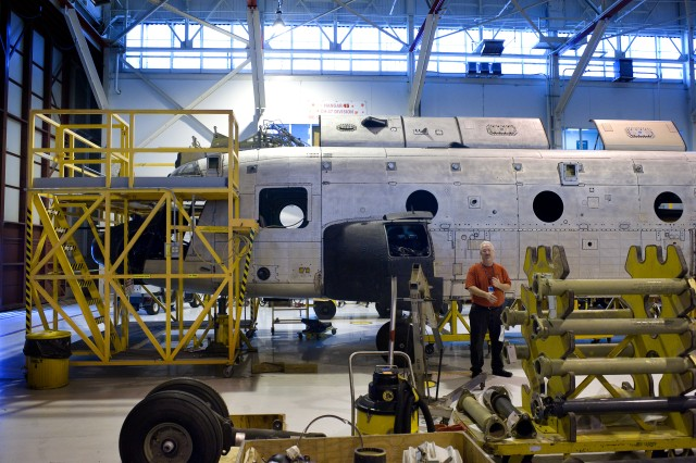 A mechanic stands next to the shell of a CH-47 Chinook helicopter while Gen. George W. Casey receives a tour of the  Corpus Christi Army Depot, TX, Jan. 10, 2011.  The depot is a US Department of Defense Center of Industrial and Technical Excellence for rotary wing aircraft.