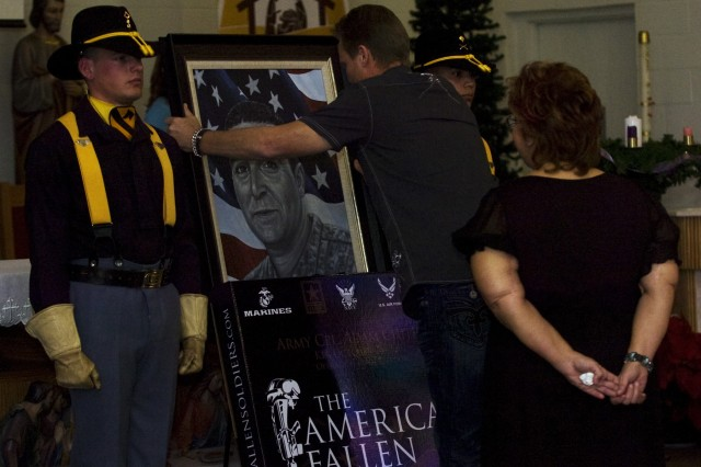 Phil Taylor, artist for and founder of The American Fallen Soldiers Project: Portraits of Patriotism, unveils a portrait of Cpl. Adam Chitjian, 3rd Battalion, 8th Cavalry Regiment, 3rd Brigade Combat Team, 1st Cavalry Division, who was killed in action in Balad, Iraq, Oct. 25, 2007, for Shirley Chitjian, Adam's wife, Jan. 7, during a memorial ceremony at the 58th Street Chapel.